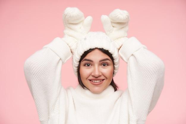 Fröhliche junge attraktive braunhaarige frau, gekleidet in weißen pullover, handschuhen und hut, während sie über rosa wand posiert, hände erhoben hält, während brötchenohren imitiert