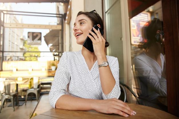 Fröhliche junge attraktive brünette frau mit brötchenfrisur, die hände auf arbeitsplatte hält, während angenehmes gespräch am telefon hat, mittagspause im stadtcafé habend