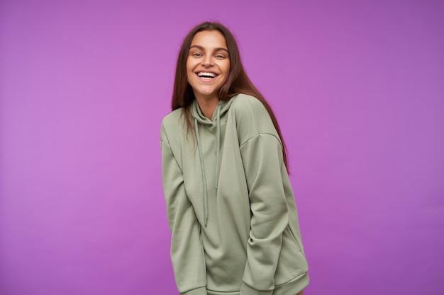 Fröhliche junge attraktive langhaarige brünette frau zeigt ihre weißen perfekten zähne, während sie glücklich lacht und über lila wand in minze hoodie steht