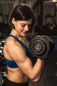 Fröhliche junge attraktive sportlerin, die gewichte im fitnessstudio hebt