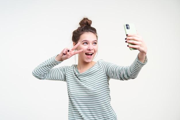 Fröhliche junge blauäugige schöne brünette frau mit brötchenfrisur, die friedenszeichen mit erhabener hand zeigt, während selfie mit ihrem smartphone, lokalisiert über weißer wand nimmt