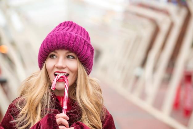 Fröhliche junge blonde frau in roter strickmütze posiert mit zuckerstange auf der straße