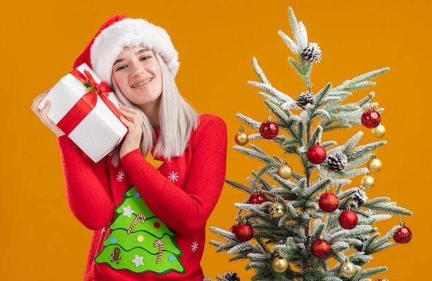 Fröhliche junge blonde frau in weihnachtspullover und weihnachtsmütze, die ein geschenk-smilin hält, das fröhlich neben einem weihnachtsbaum über orangefarbener wand steht