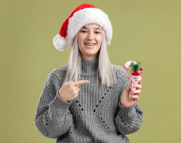 Fröhliche junge blonde frau in winterpullover und weihnachtsmütze mit weihnachtszuckerstange, die mit dem zeigefinger darauf zeigt, fröhlich lächelnd über grüner wand stehend