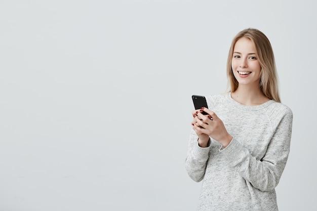 Fröhliche junge blonde frau mit niedlichem lächeln, das drinnen aufwirft, handy benutzt, newsfeed auf ihren konten des sozialen netzwerks prüfend. hübsche frau, die internet auf dem handy surft