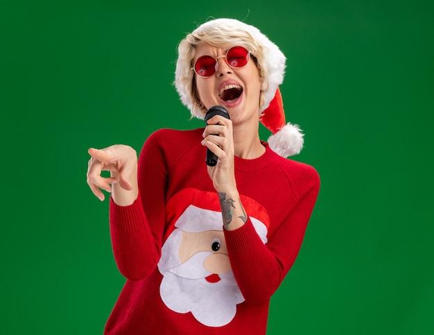 Fröhliche junge blonde frau mit weihnachtsmütze und weihnachtsmann-weihnachtspullover mit brille, die das mikrofon hält und mit geschlossenen augen singt, isoliert auf grüner wand mit kopierraum