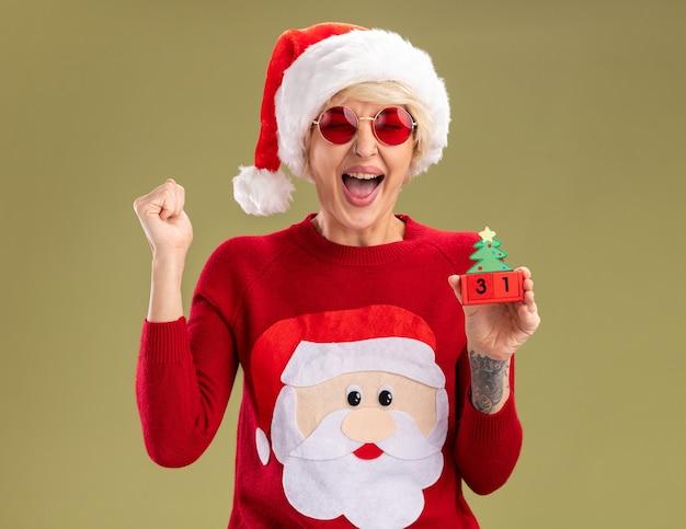 Fröhliche junge blonde frau mit weihnachtsmütze und weihnachtsmann-weihnachtspullover mit brille, die weihnachtsbaumspielzeug mit datum hält, das ja-geste mit geschlossenen augen isoliert auf olivgrüner wand macht