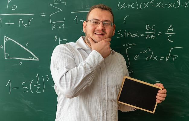 Fröhliche junge blonde lehrerin mit brille, die vor der tafel im klassenzimmer steht und eine mini-tafel hält, die die hand am kinn hält und in die kamera schaut