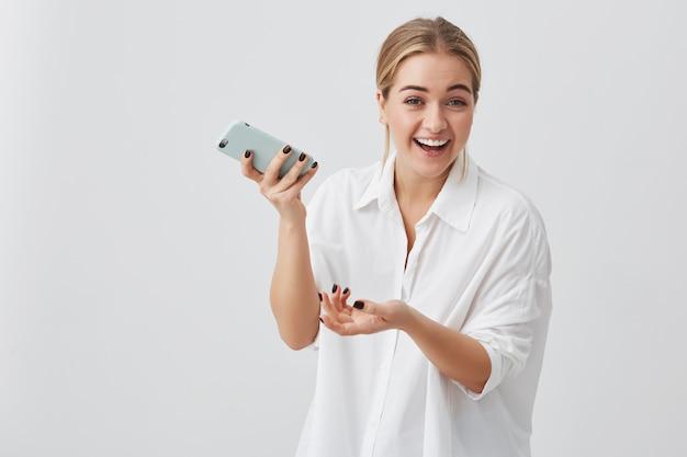 Fröhliche junge blonde studentin, die freudig mit den zähnen mit dem handy lächelt und newsfeed auf ihren konten des sozialen netzwerks überprüft. hübsches mädchen, das internet auf dem handy surft