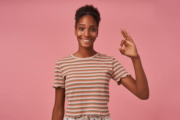 Fröhliche junge braunäugige hübsche brünette frau, die ok geste zeigt, während sie glücklich mit breitem lächeln schaut, isoliert über rosa wand in freizeitkleidung