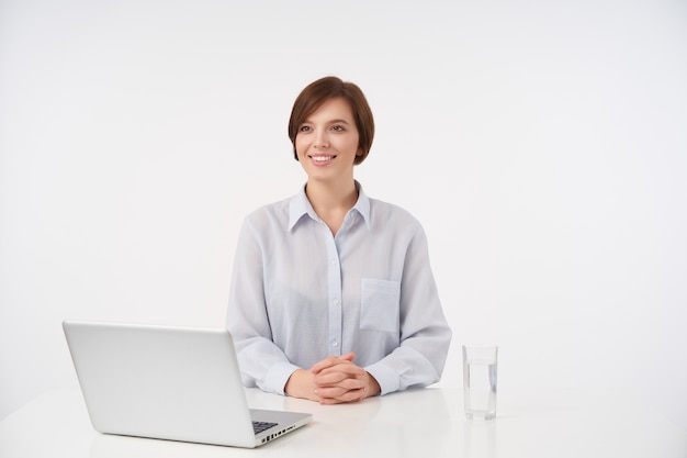 Fröhliche junge braunhaarige mitarbeiterin, die auf weiß mit modernem laptop sitzt und bereit ist, sich zu treffen, mit positivem lächeln beiseite schauend