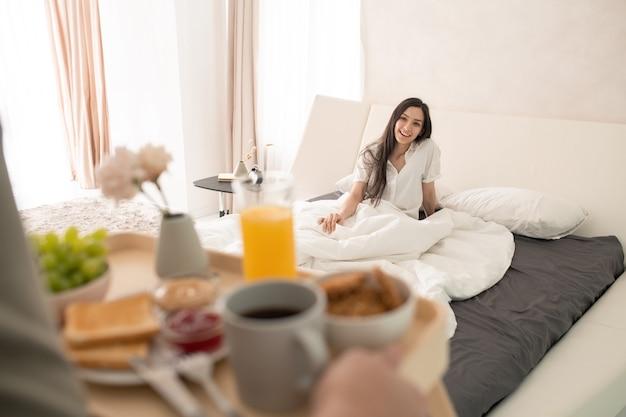 Fröhliche junge brünette frau, die unter einer weißen decke auf einem großen doppelbett sitzt und ihren mann mit einem tablett mit frühstück betrachtet