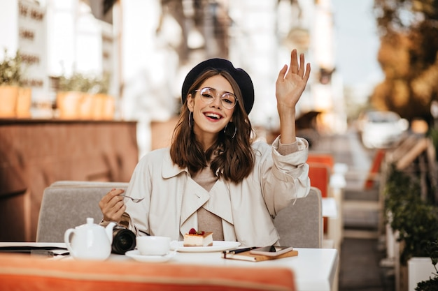Fröhliche junge brünette mit baskenmütze, beigefarbenem trenchcoat und stilvoller brille, die am sonnigen herbsttag auf der terrasse des stadtcafés sitzt, käsekuchen isst und nach kellner ruft
