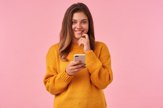 Fröhliche junge charmante brünette dame mit lässiger frisur, die angenehm lächelt und unterlippe beißt, während sie positiv schaut, handy hält, während auf rosa posiert