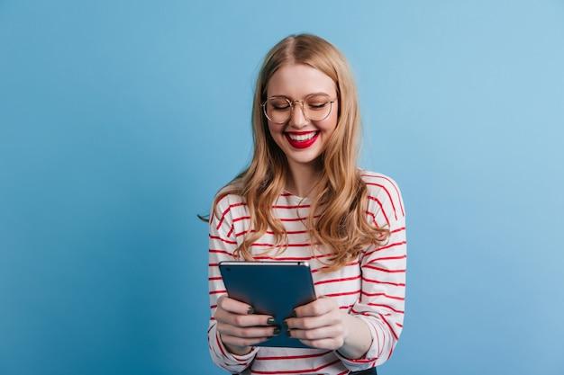Fröhliche junge dame, die digitales tablett mit lächeln hält. studioaufnahme der niedlichen dame in der freizeitkleidung lokalisiert auf blauem hintergrund.