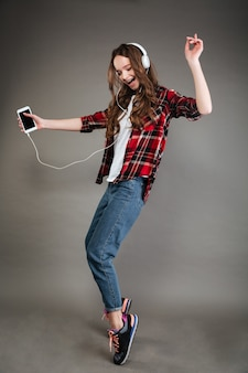 Fröhliche junge dame, die musik mit kopfhörern beim tanzen hört.