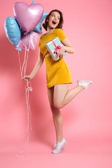 Fröhliche junge dame im gelben kleid, das ballons mit geschenk hält