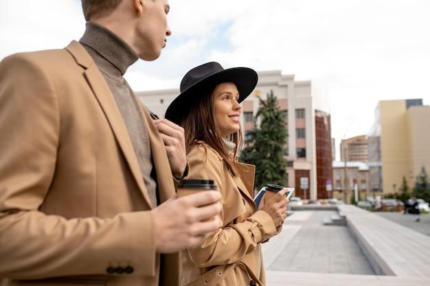 Fröhliche junge dates in beiger freizeitkleidung mit kaffee unterwegs in der städtischen umgebung gegen gebäudegruppe und modernen park