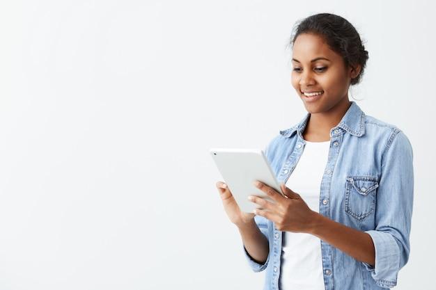 Fröhliche junge dunkelhäutige studentin mit niedlichem lächeln, das auf weißer wand steht, tablette benutzt, newsfeed auf ihren konten des sozialen netzwerks prüfend. hübsches afroamerikanisches mädchen, das internet auf t surft