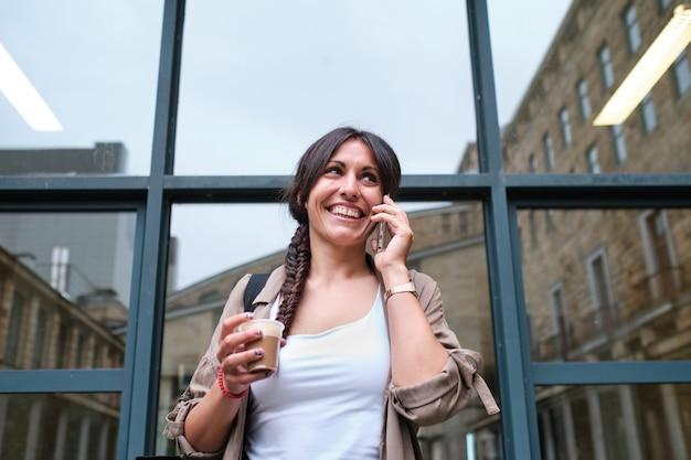 Fröhliche junge erwachsene frau, die mit ihrem telefon spricht, während sie einen kaffee mit fenstern auf der rückseite trinkt, die die gebäude draußen widerspiegeln?