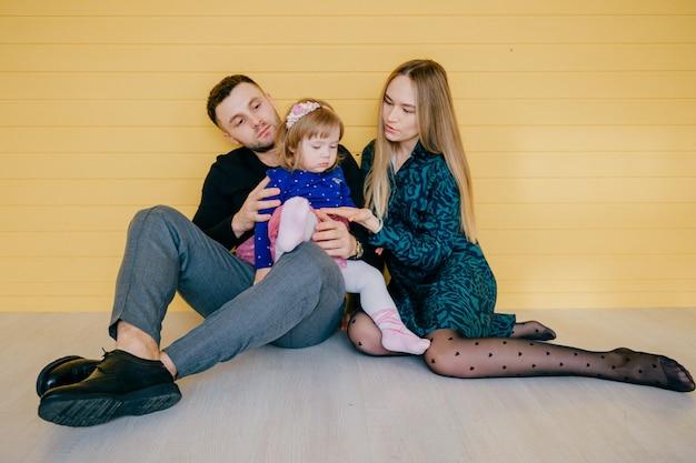 Fröhliche junge familie mit einem weiblichen kind, das spaß zusammen über gelber wand hat.
