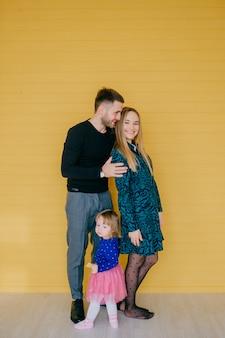 Fröhliche junge familie mit reizender kleiner tochter, die spaß zusammen über gelber wand hat