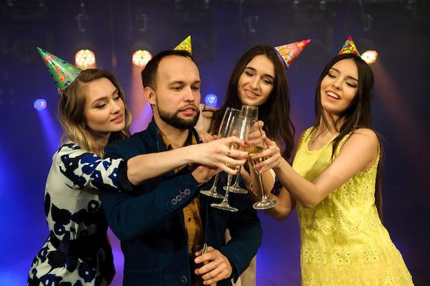 Fröhliche junge firma feiert geburtstag in einem nachtclub