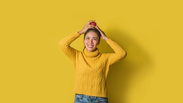 Fröhliche junge frau auf gelbem hintergrund im studio. ein lächelndes und glückliches mädchen mit einem apfel, der auf ihrem kopf stillsteht. das konzept der bewegung für eine gute gesundheit. gesundheitsliebhaber