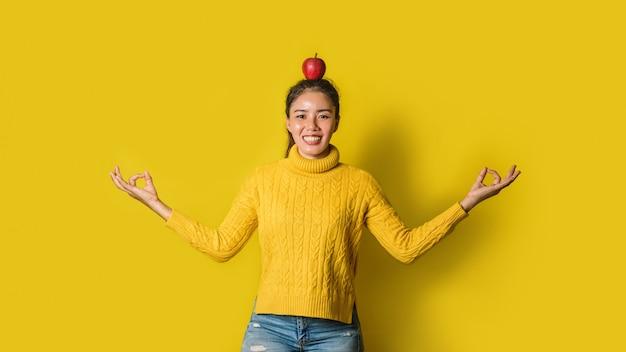 Fröhliche junge frau auf gelbem hintergrund im studio. ein mädchen mit einem apfel, der beim yoga auf dem kopf ruht. das konzept der bewegung für eine gute gesundheit. gesundheitsliebhaber