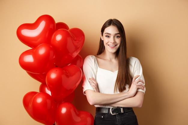 Fröhliche junge frau, die am valentinstag glücklich aussieht, steht in der nähe von herzballons mit verschränkten armen...