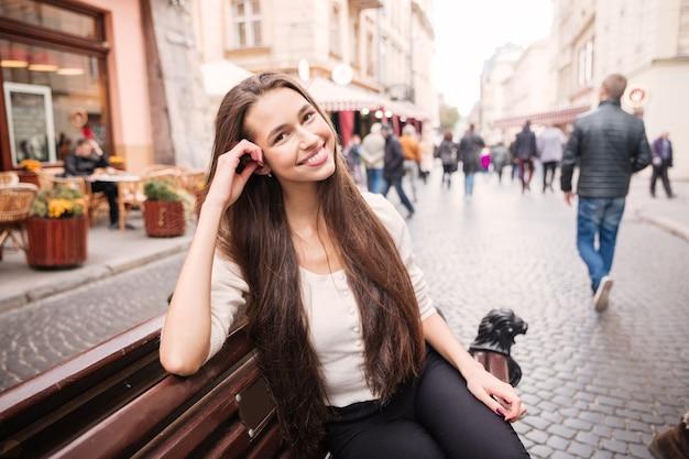 Fröhliche junge frau, die auf der bank in der altstadt sitzt und lächelt