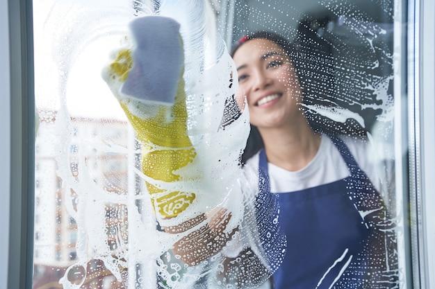 Fröhliche junge frau, die beim fensterputzen lächelt, glasoberfläche mit schwamm. hausarbeit und hauswirtschaft, reinigungsservice-konzept. blick durch das glas