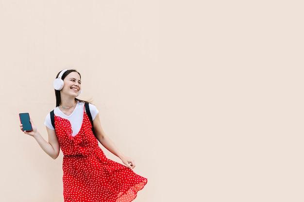 Fröhliche junge frau, die beim tanzen musik mit kopfhörern auf dem handy hört