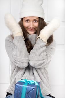 Fröhliche junge frau, die ein geschenk mit blauem band halten