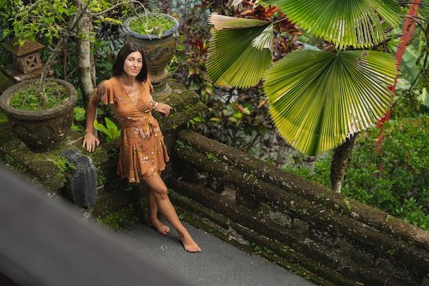 Fröhliche junge frau, die ein lächeln auf dem gesicht behält und ihren urlaub im exotischen land genießt