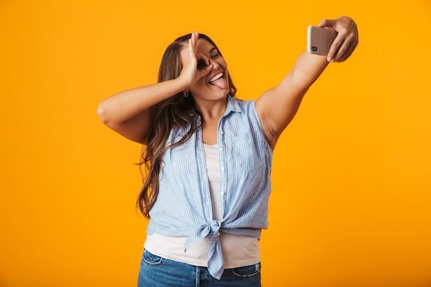 Fröhliche junge frau, die ein selfie mit ausgestreckter hand nimmt