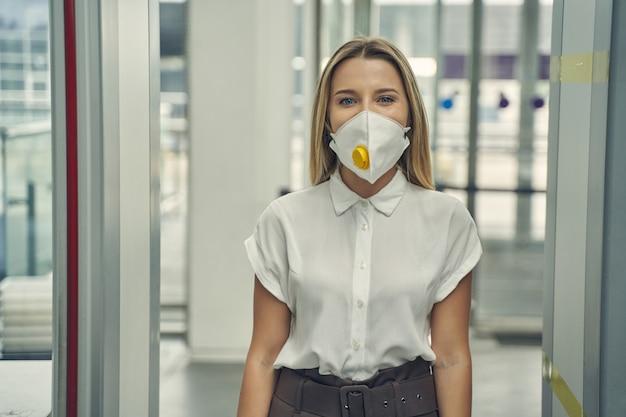 Fröhliche junge frau, die eine schutzmaske auf ihrem gesicht hält, während sie durch den metalldetektor geht