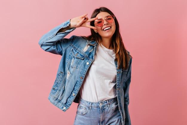 Fröhliche junge frau, die friedenszeichen mit lächeln zeigt. studioaufnahme der attraktiven kaukasischen dame, die jeanskleidung trägt.