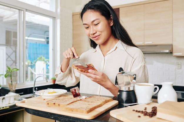 Fröhliche junge frau, die geleesandwich für frühstück macht