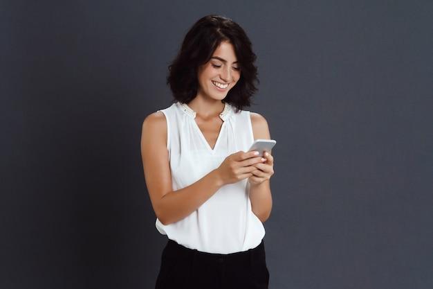 Fröhliche junge frau, die ihr telefon in den händen hält