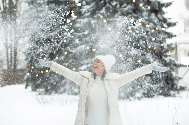 Fröhliche junge frau, die im wald mit schnee spielt
