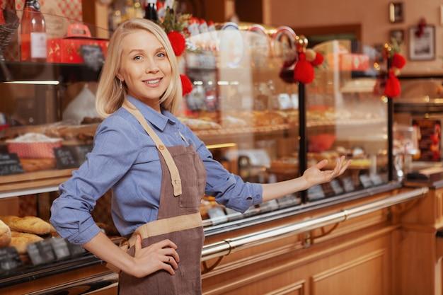 Fröhliche junge frau, die junge in ihrem bäckereigeschäft begrüßt. glückliche bäckerin, die an ihrem geschäft arbeitet