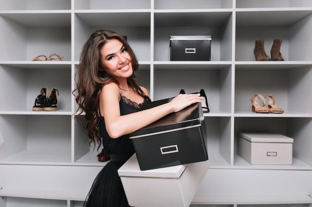 Fröhliche junge frau, die kisten mit schuhen in händen hält, im luxusgarderobe stehend, ankleidezimmer. sie ist glücklich, lächelt und schaut. trage ein schönes schwarzes kleid.