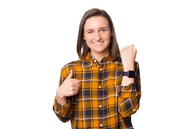 Fröhliche junge frau, die lokalisiert auf weißem hintergrund aufwirft. smart watch zur hand tragen