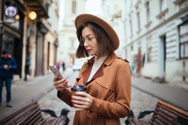 Fröhliche junge frau, die mantel trägt, der draußen geht und kaffeetasse zum mitnehmen hält