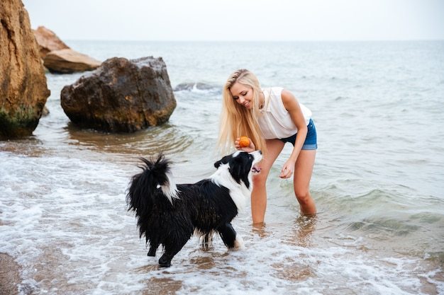 Fröhliche junge frau, die mit hund am meer spielt