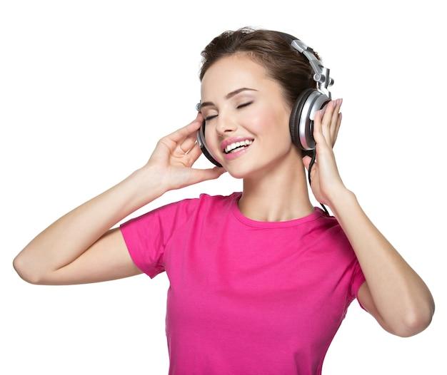 Fröhliche junge frau, die musik mit kopfhörern hört