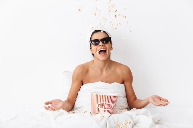 Fröhliche junge frau, die nach der dusche im bett sitzt, in eine decke gehüllt, eine sonnenbrille trägt und popcorn isst