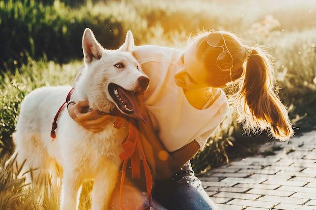 Fröhliche junge frau, die niedlichen hund streichelt, während auf ziegelpfad während des spaziergangs in der natur sitzt