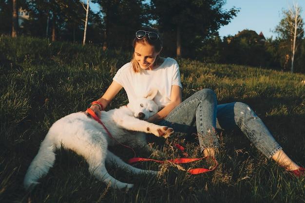 Fröhliche junge frau, die pelzigen weißen hund beim sitzen auf gras in der schönen natur streichelt